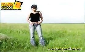 Teen peeing in grass.