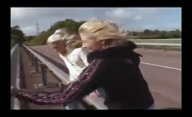 Two blonde girls wetting panties on bridge above highway